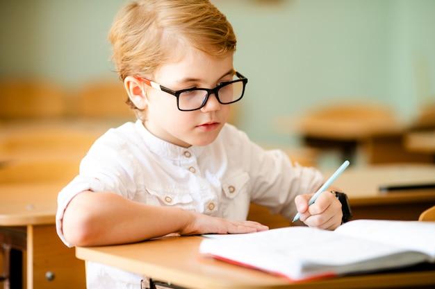 Zeven jaar oud kind dat met glazen zijn huiswerk op school schrijft Premium Foto
