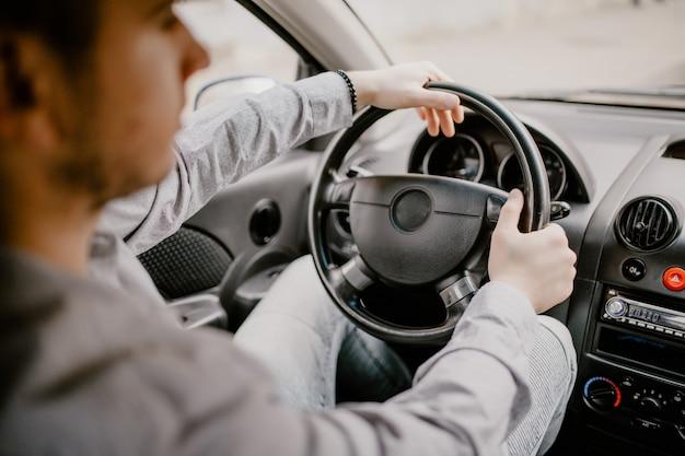Zich concentreren op de weg. achtermening van de jonge knappe mens die recht terwijl het drijven van een auto kijken Gratis Foto