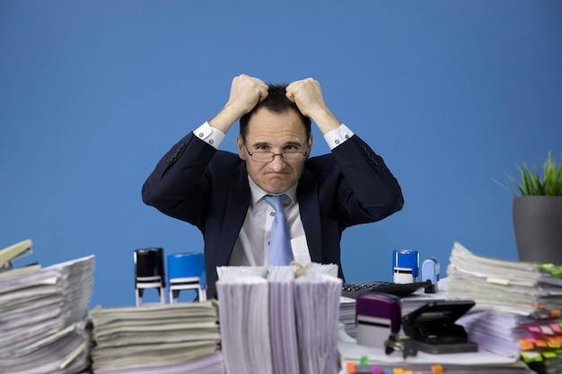 Zich moe en overwerkt voelen zakenman scheurt zijn haar gestrest op een bureau vol papierwerk Premium Foto