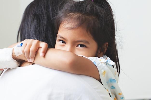 Ziek aziatisch kindmeisje dat iv-oplossing heeft verbonden knuffelen haar moeder met liefde in het ziekenhuis Premium Foto