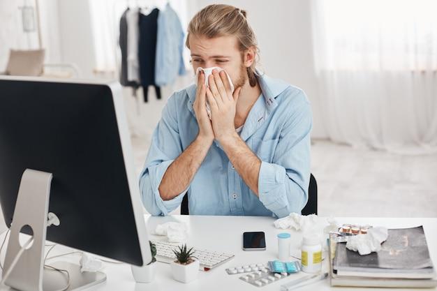 Ziek en moe, bebaarde kantoormedewerker heeft last van expressie, heeft een loopneus, niest, hoest door griep, omringd door pillen en drugs, probeert zich te concentreren en het werk sneller af te maken Gratis Foto