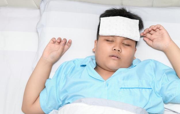 Ziek kind dat met hoge koorts in bed legt. Premium Foto