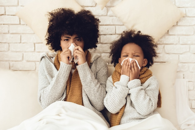 Zieke afrikaanse moeder en dochter zitten op bed. Premium Foto