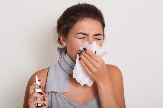 Zieke allergische vrouw blaast een lopende neus, griep of verkoudheid, niezen in zakdoek, poseren met gesloten ogen geïsoleerd op wit, neusspray in de hand houden. Gratis Foto