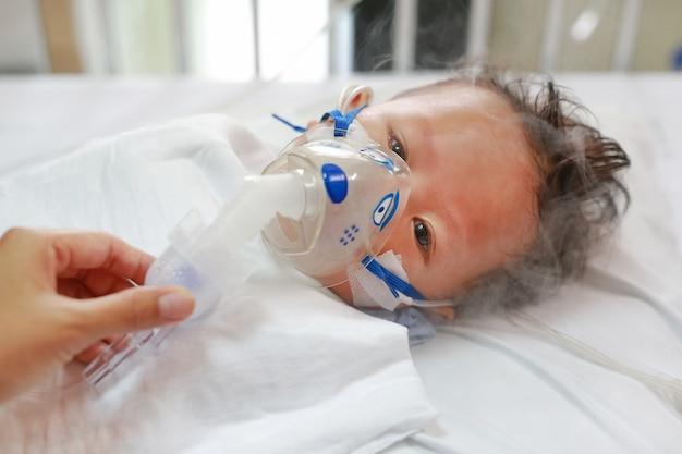 Zieke babyjongen die medicatie inhaleert door inhalatiemasker om te genezen respiratory syncytial virus (rsv) Premium Foto