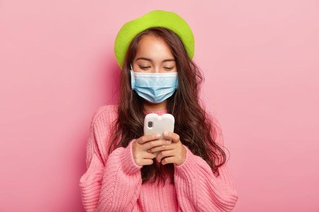 Zieke jonge brunette vrouw met donker haar, gericht in mobiel apparaat, draagt medische masker, heeft problemen met de gezondheid Gratis Foto