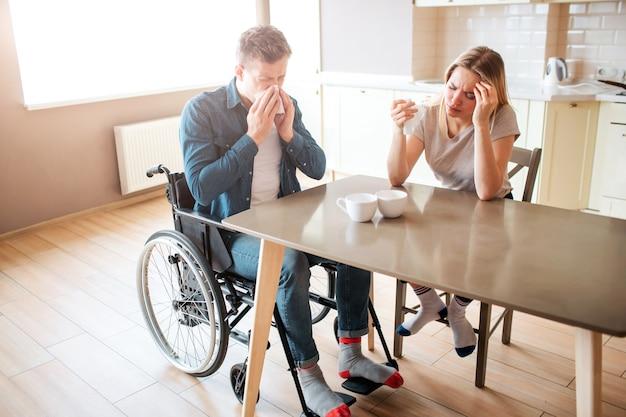 Zieke jonge man met inclusiviteit niezen met gezonde vrouw aan tafel Premium Foto