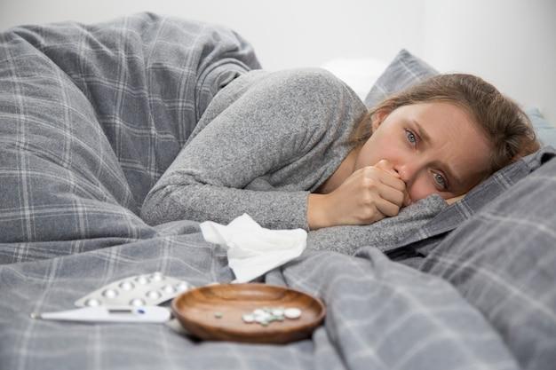 Zieke jonge vrouw liggend in bed, hoesten Gratis Foto