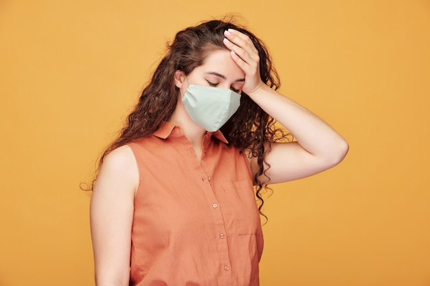 Zieke jonge vrouw met hoofdpijn in beschermend masker haar hoofd aan te raken terwijl ze zich onwel voelt Premium Foto