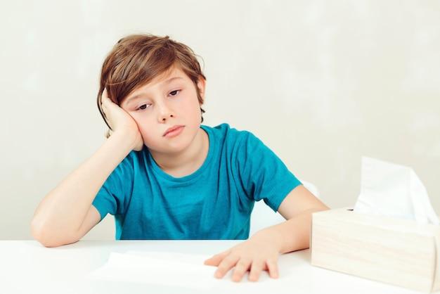 Zieke jongenszitting bij bureau. kid met behulp van papieren servetten. allergisch kind, griepseizoen. jongen heeft een virus, loopneus en hoofdpijn. Premium Foto