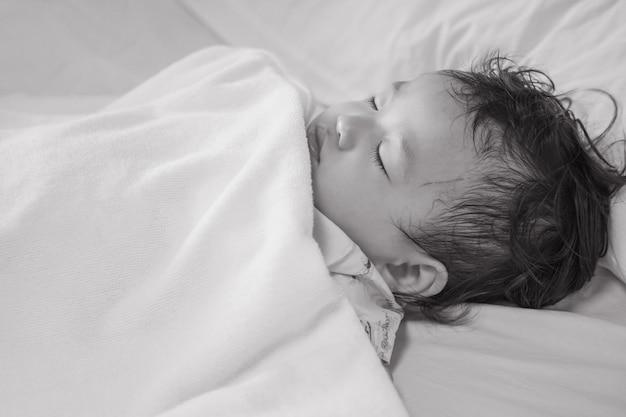 Zieke kindslaap op de geweven achtergrond van het het ziekenhuisbed in zwart-witte toon Premium Foto