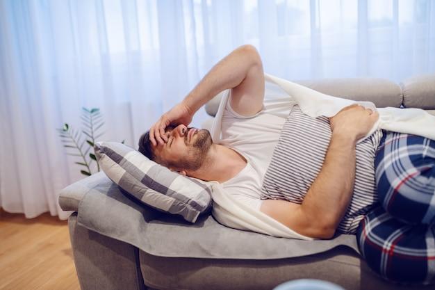 Zieke knappe blanke man in pyjama liggend op de bank in de woonkamer en buikpijn. Premium Foto