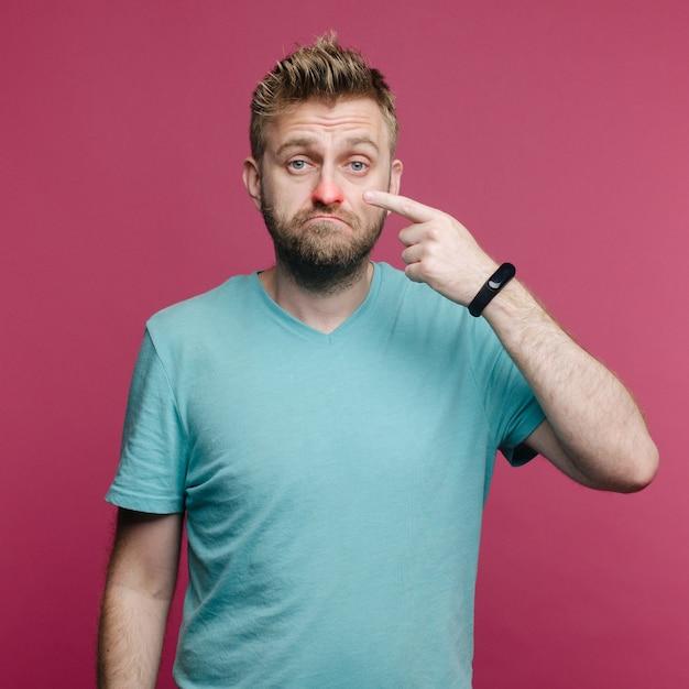 Zieke man heeft een loopneus. man maakt een remedie voor verkoudheid van de airconditioner Premium Foto