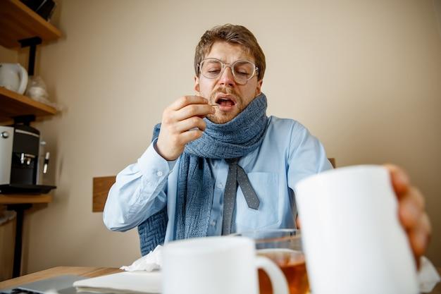Zieke man tijdens het werken op kantoor, zakenman verkouden, seizoensgriep. Gratis Foto