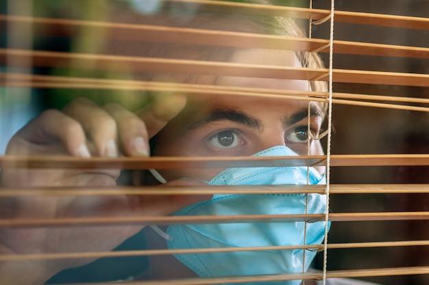 Zieke man van corona-virus kijkt door het raam en draagt maskerbescherming en herstel van de ziekte thuis. quarantaine. Premium Foto
