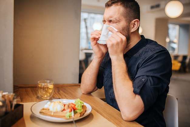 Zieke man zit aan de tafel en niest. hij bedekt zijn neus met een wit servet en houdt de ogen gesloten. de mens is erg ziek. Premium Foto