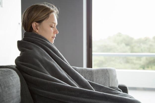 Zieke vrouw die haar ogen gesloten houdt, die thuis mediteert Gratis Foto