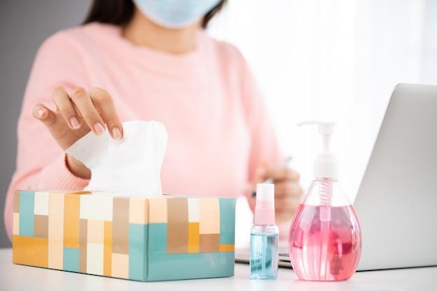 Zieke vrouw die wit tissuepapier neemt terwijl hoest voor preventie coronavirus (covid-19). Premium Foto