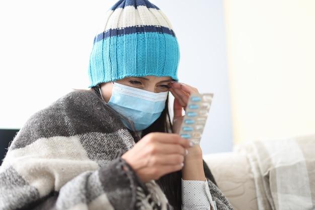 Zieke vrouw in hoed onder deken op zelfisolatie houdt pillen in haar handen Premium Foto