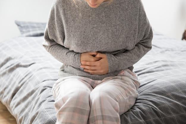 Zieke vrouw met handen op maag die aan intense pijn lijdt Gratis Foto