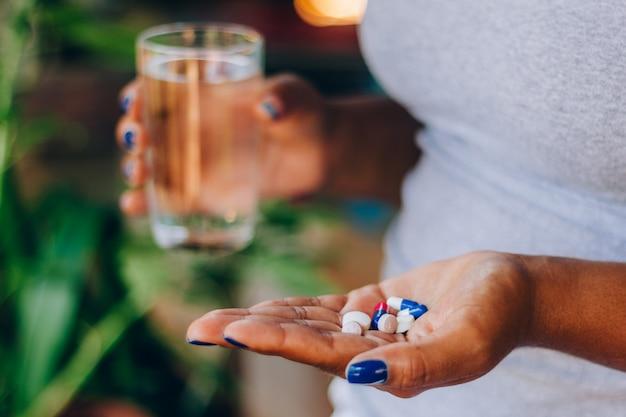 Zieke vrouw met verschillende medicijnen in haar handpalm en een glas water. medicijnen nemen. concept van persoon en zelfmedicatie. gezondheid behandeling Premium Foto