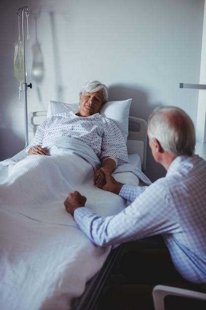 Zieke vrouw slapen op bed terwijl bezorgd man zit naast haar bed Gratis Foto