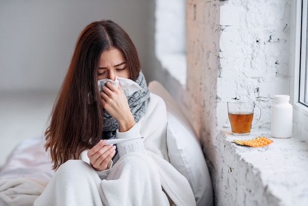 Zieke vrouw verkouden, ziek voelen en niezen op papier afvegen Premium Foto