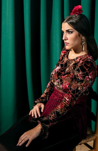 Zigeunervrouw die op een stoel zit en weg kijkt Gratis Foto