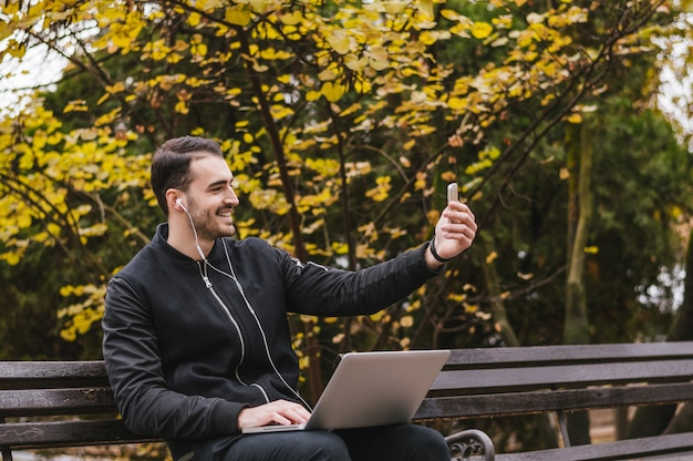 Zij beeld van een gelukkige kerel die een slimme telefoonzitting op een bank in een park gebruikt Premium Foto