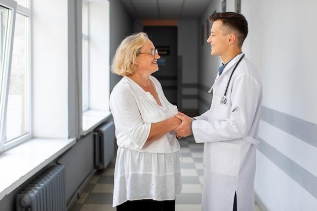 Zijaanzicht arts hand in hand van de patiënt Gratis Foto