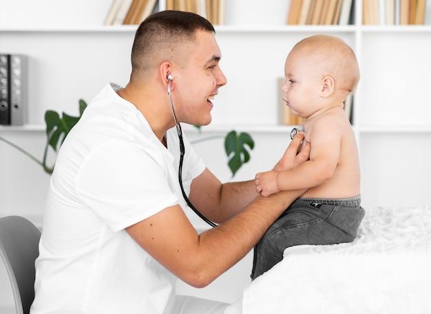 Zijaanzicht arts luisteren kleine baby met stethoscoop Gratis Foto