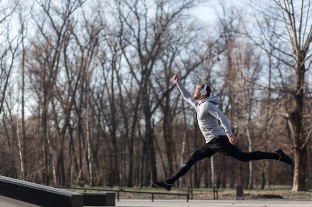 Zijaanzicht atletische man loopt buiten Gratis Foto
