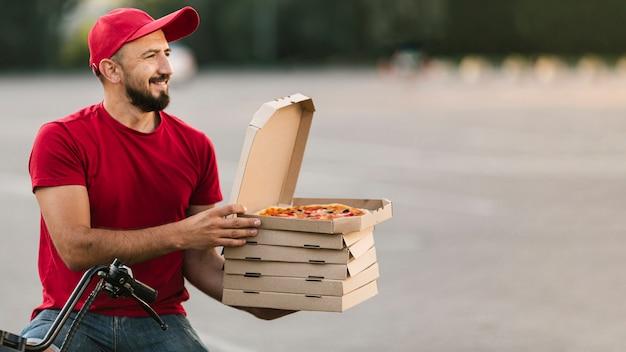 Zijaanzicht bezorger met motorfiets en pizza Gratis Foto