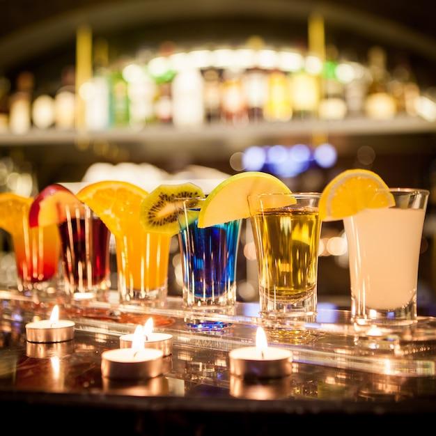 Zijaanzicht cocktail shots met schijfje citroen en appel schijfje en kaarsen op bar Gratis Foto