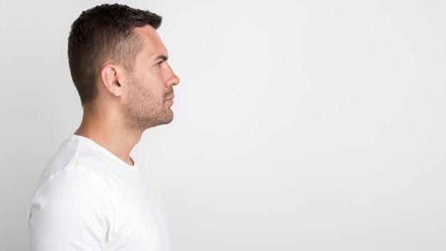 Zijaanzicht dat van de jonge mens zich tegen witte achtergrond bevindt Gratis Foto