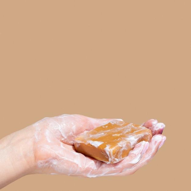 Zijaanzicht dat van hand schuimende zeep met exemplaarruimte houdt Gratis Foto