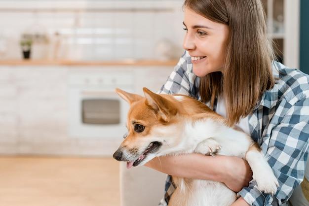 Zijaanzicht dat van hond door vrouw wordt gehouden Gratis Foto