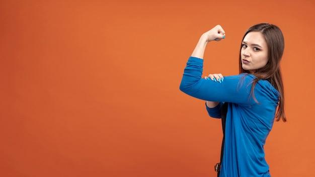 Zijaanzicht dat van vrouw haar biceps met exemplaarruimte toont Gratis Foto