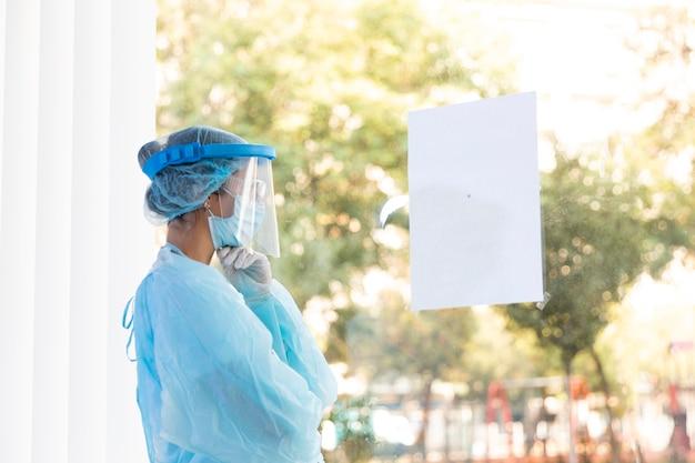 Zijaanzicht doordachte dokter vrouw in beschermende kleding Gratis Foto