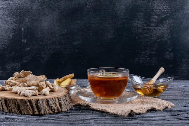 Zijaanzicht een thee met gember, plakjes en honing op zakdoek en donkere houten achtergrond. horizontaal Gratis Foto