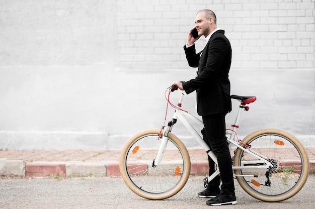 Zijaanzicht elegant mannetje met fiets in openlucht Premium Foto
