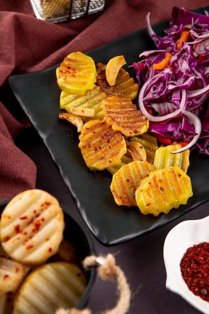 Zijaanzicht gegrilde aardappelen met rode ui kool rode oranje paprika's en gedroogde chili vlokken op donkergrijze achtergrond Gratis Foto