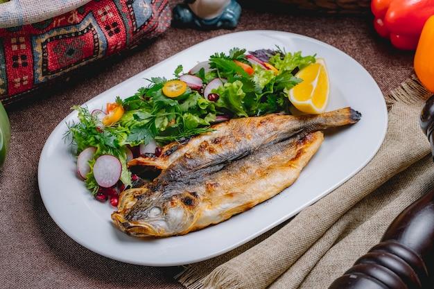 Zijaanzicht gegrilde vis met een salade van groenten en kruiden met een schijfje citroen Gratis Foto