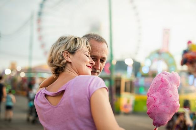 Zijaanzicht gelukkig paar met roze gesponnen suiker Gratis Foto