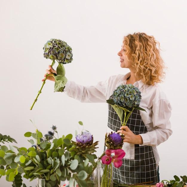 Zijaanzicht gelukkige bloemist die twee boeketten steunt Gratis Foto