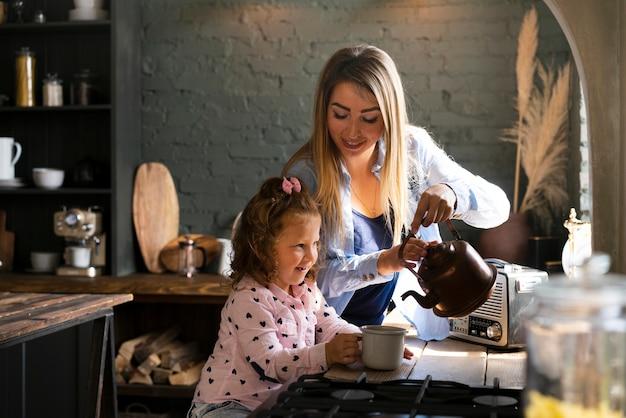 Zijaanzicht gelukkige moeder en dochter in de keuken Gratis Foto