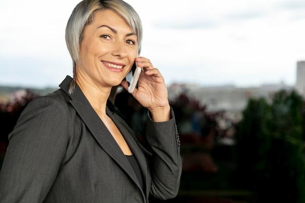 Zijaanzicht glimlach vrouw praten over de telefoon Gratis Foto