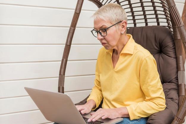 Zijaanzicht hogere vrouw die aan haar laptop werkt Gratis Foto