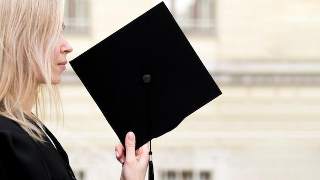 Zijaanzicht jonge vrouw die haar afstuderen viert Premium Foto