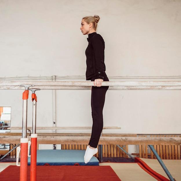 Zijaanzicht jonge vrouw training voor gymnastiek kampioenschap Gratis Foto
